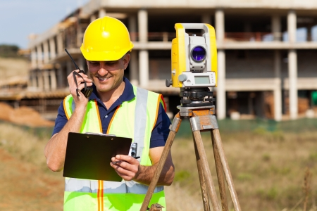 walkie talkie: senior land surveyor talking on walkie talkie