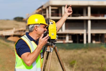 surveyor: agrimensor mayor hablando por walkie talkie en sitio de construcción Foto de archivo