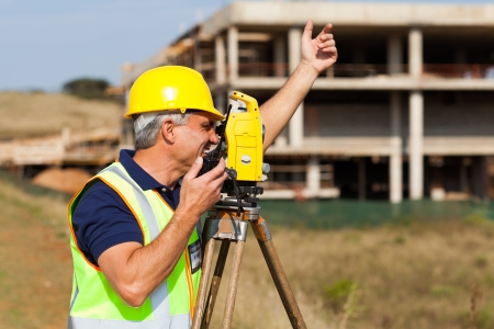 walkie: senior land surveyor talking on walkie talkie at construction site