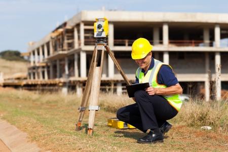 land surveyor: middle aged land surveyor working outdoors Stock Photo