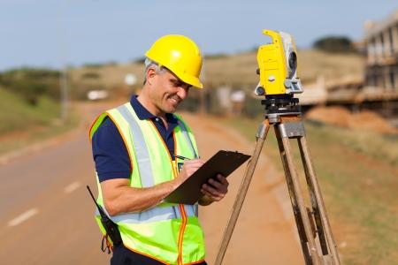 theodolite: geometra anziano a lavorare sulla strada
