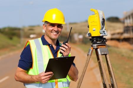 land surveyor: senior land surveyor working at road construction site