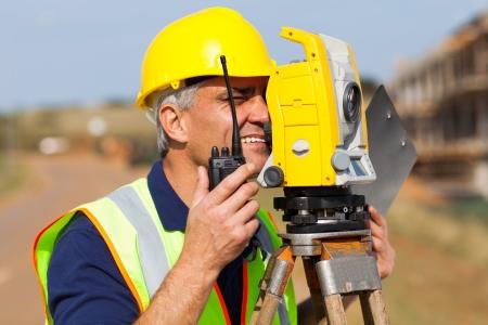 teodolito: agrimensor mayor que trabaja con taquímetro en el sitio de construcción Foto de archivo