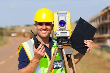 gelukkig senior landmeter met tacheometer op bouwwerf Stockfoto