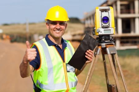 teodolito: topógrafo mayor que da el pulgar para arriba en el sitio de construcción Foto de archivo