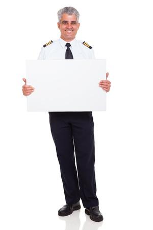 experienced: smiling senior airline pilot captain holding white board on white background Stock Photo