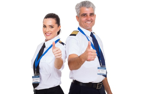 airline uniform: cheerful airline pilots giving thumbs up over white background Stock Photo