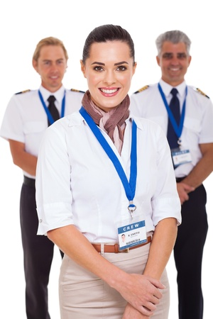 attractive airhostess standing in front of pilots on white background photo