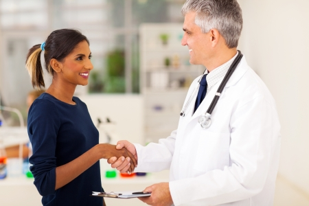 friendly senior doctor handshaking with indian patient in office photo
