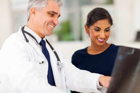 doctor visit: happy senior doctor examining patients x-ray  Stock Photo