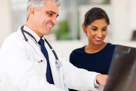 doctor visit: happy senior doctor examining patients x-ray  Stock Photo