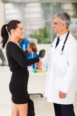 personen: mooie medische rep handshaking met senior arts