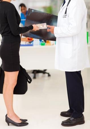 sales representative: medical rep bribing doctor, hiding money behind x-ray Stock Photo