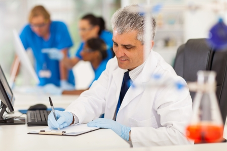 cheerful middle aged medical researcher working in lab photo