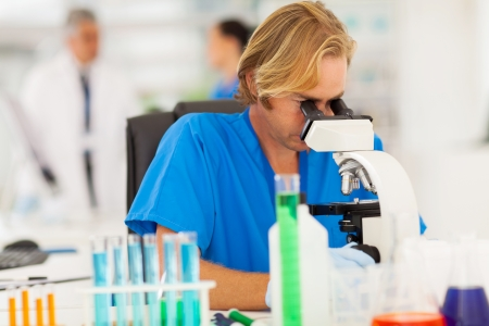 pharmacology: male scientist looking through microscope in the lab Stock Photo