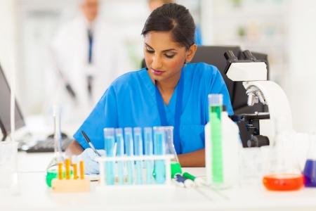 investigador cientifico: hermosa joven india informe escrito investigador m�dico en el laboratorio
