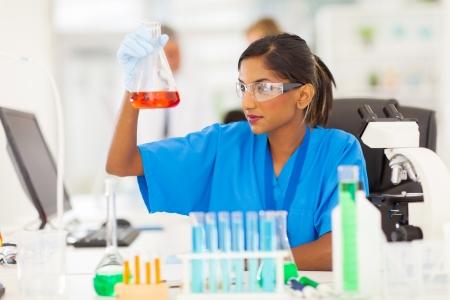 플라스크에서 아름 다운 젊은 인도 의료 연구원의 분석 액체 스톡 콘텐츠