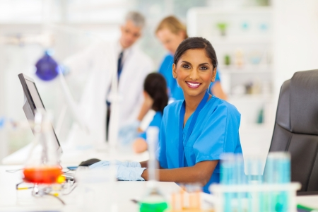 clinical research: cheerful indian laboratory worker using computer in lab