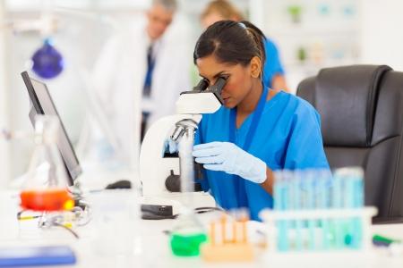investigador cientifico: joven investigador m�dico indio mirando a trav�s de microscopio en laboratorio Foto de archivo