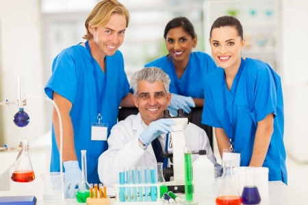 cheerful senior scientist with group of chemistry students in the lab photo