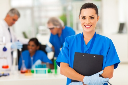 lab technician: attractive young female lab technician in lab with colleagues Stock Photo