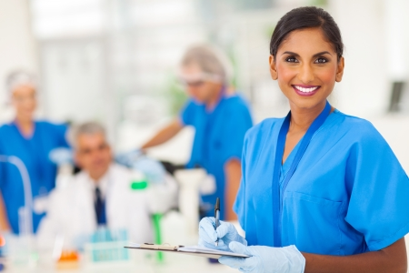 cheerful young indian medical researcher writing report in the lab photo