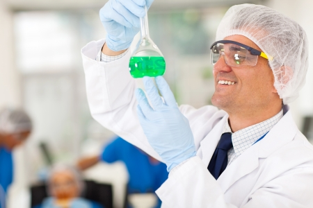 cheerful senior chemist working in lab photo