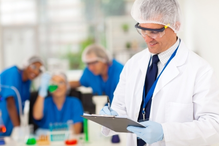 smart senior scientist writing medical report in the lab photo
