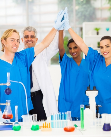 successful team of scientists high five in lab photo