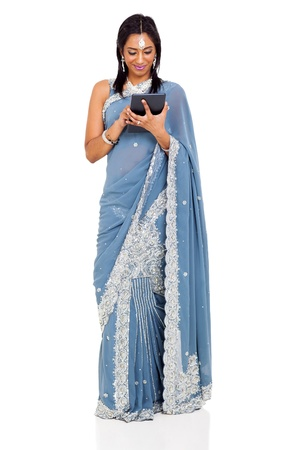 pretty indian woman in saree using tablet computer isolated on white photo
