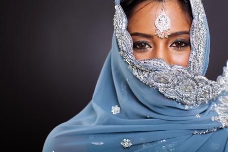 그녀의 얼굴을 가진 사리에 젊은 인도 여자는 검은 색 바탕에 덮여