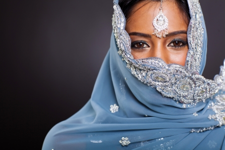 young indian woman in sari with her face covered on black background Stock Photo