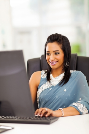 happy indian woman in traditional clothing using computer at work Stock Photo - 21123033