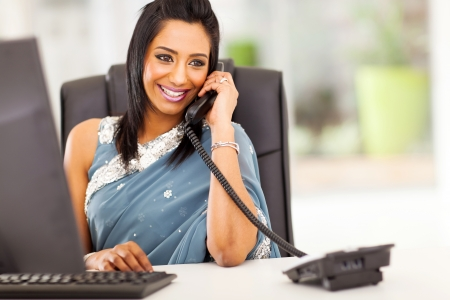 recepcionista: atractiva recepcionista indio joven hablando por tel�fono