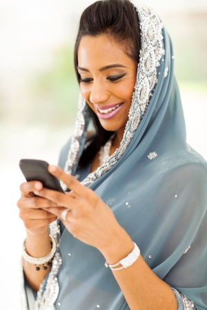 smiling indian woman in traditional clothes reading emails on smart phone photo