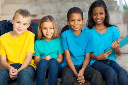 multiracial groups: group of smiling primary school students outdoors