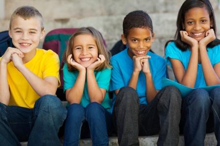 multicultureel: vrolijke lagere school kinderen zitten buiten Stockfoto