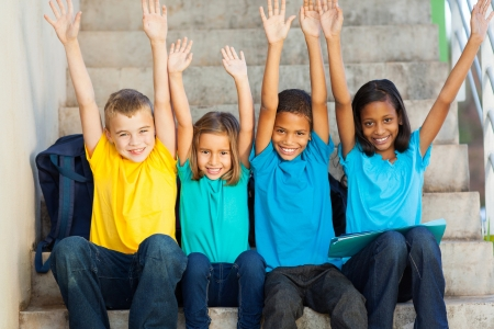 group of happy primary students with hands raised sitting outdoors