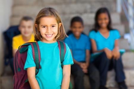 niño con mochila: chica bonita preescolar con compañeros de escuela en el fondo