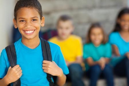 niño con mochila: alegre niño de la escuela primaria afroamericana con mochila Foto de archivo
