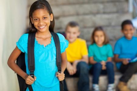 escuela primaria: Retrato de una hermosa ni�a de la escuela primaria con compa�eros de escuela en el fondo