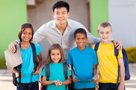 asian teacher: four elementary school students and teacher on campus