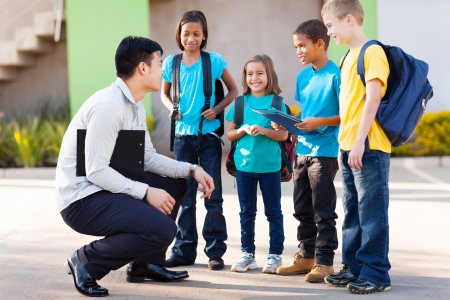 multi ethnic children: cute elementary pupils outside classroom talking to teacher