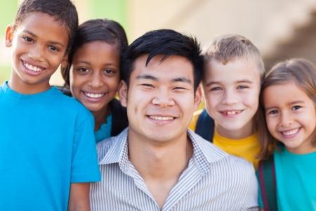 escuela primaria: cerca retrato de profesor feliz con los alumnos de primaria Foto de archivo