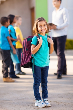 elementary school student: happy primary school student carrying backpack with classmates and teacher on background