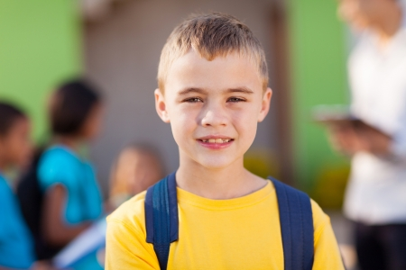 cute male elementary pupil outside classroom photo