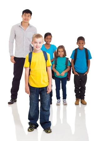 multiracial children: cute school boy standing in front of classmates and teacher on white background