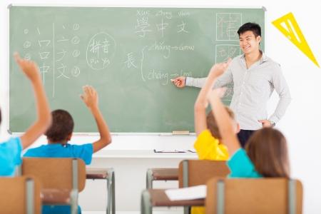educators: sonriendo educador enseñanza del idioma chino al grupo de niños de primaria