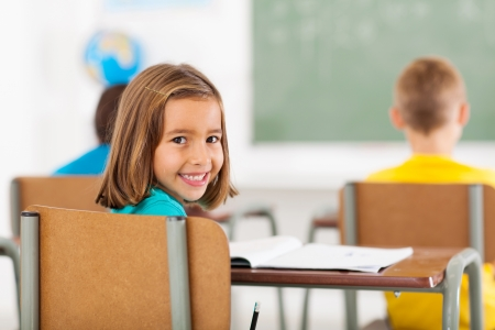 cheerful adorable little schoolgirl in classroom looking back photo