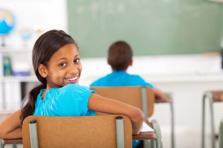 indian school girl: cute primary school girl in classroom looking back Stock Photo